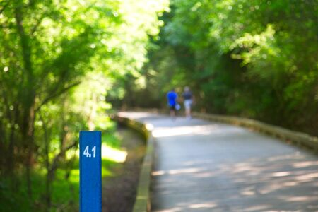 Mile Marker with Couple Walking in Background Stock Photo