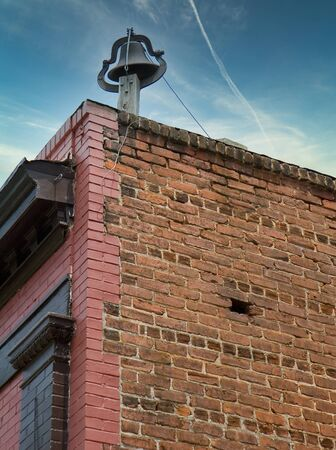 An old brick building with an old bell on top