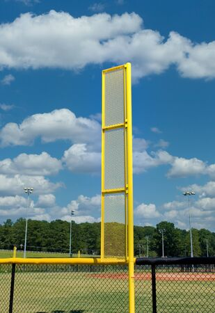 A bright yellow foul ball pole in a baseball field against blue sky 写真素材