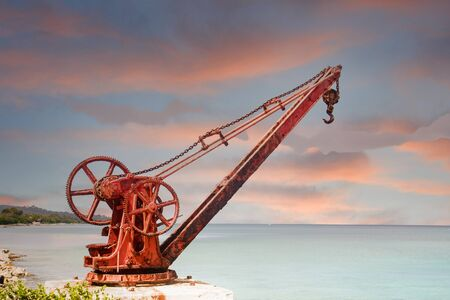 Old Red Rusty Crane on Shore at Dusk Foto de archivo