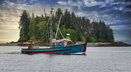 A blue shrimp boat trolling the grey waters of Alaska