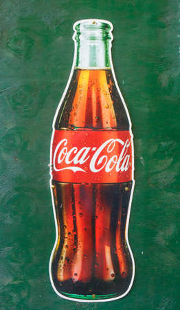 Coca Cola Sign on Green Wall