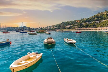 Small Boats Moored in Calm Blue Bay at Sunset Foto de archivo