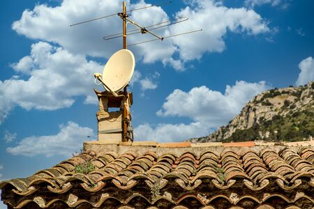Old TV Antenna and Modern Dish on Tile Roof