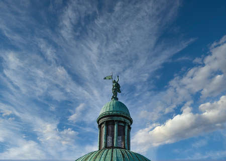 Old Statue on Green Cupola Against Blue Sky