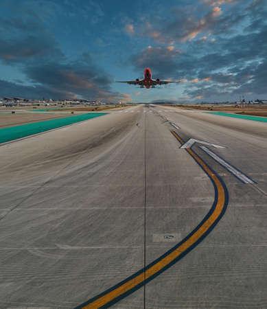 Plane Landing on Runway at Sunset