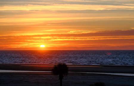 Orange Sunrise Beyond Beach Фото со стока