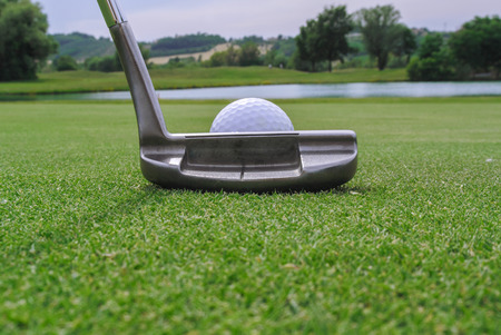 putter: a golf ball and a putter in a beautiful green Stock Photo