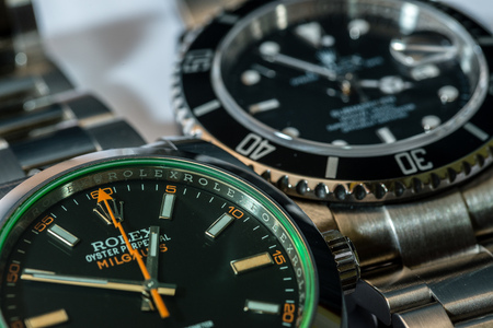 luxury watches: SAN MARINO- NOVEMBER 22 2016: A Rolex Milgauss and a Rolex Submariner in a macro view. Rolex was founded in 1909. It produces about 2,000 luxury watches daily.