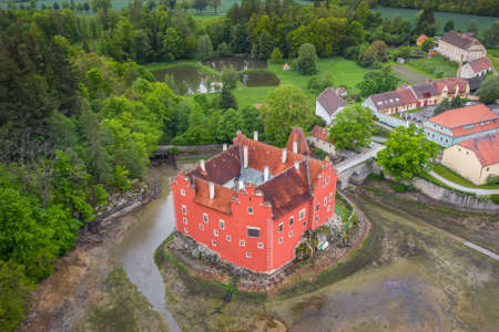 Cervena Lhota Chateau. It stands at the middle of a lake on a rocky island. Its picturesque Renaissance is a destination of thousands of tourists every year. Stok Fotoğraf - 124660617