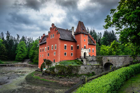 Cervena Lhota Chateau. It stands at the middle of a lake on a rocky island. Its picturesque Renaissance is a destination of thousands of tourists every year. Stok Fotoğraf - 124660623