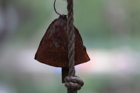 Old cowbell hanging with rope in isolation Stock Photo