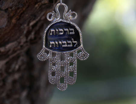 A good luck Jewish Hamsa with Best Wishes written in Hebrew hanging from a tree in isolation
