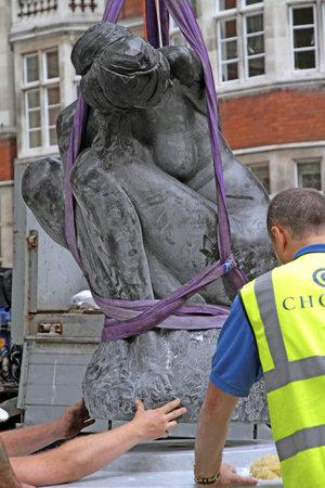 London,Mayfair UK, June 24 2011: Workmen lower a statue of female onto a plinth.