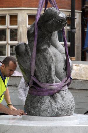 London,Mayfair UK, June 24 2011: Workmen lower an Emilio Greco statue of female onto a plinth.