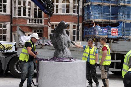 London,Mayfair UK, June 24 2011: Workmen lower a statue of female onto a plinth. Stock Photo - 9890415