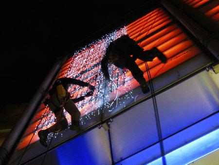 London,UK, June 2011: Workmen fix lights to modern building at night.