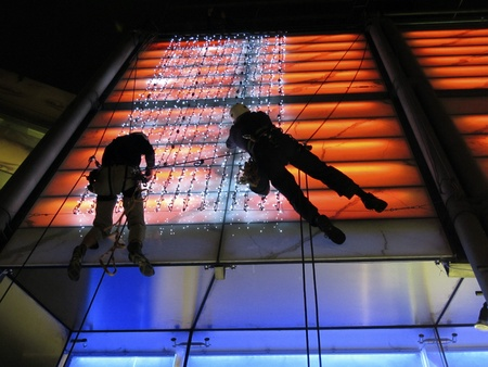 London, Oxford Street, June 2011: Workmen working overhead fixing lights at night. Editorial