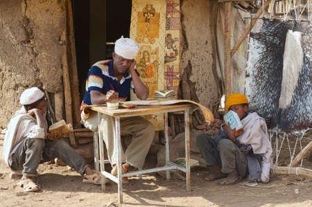illiteracy: Lalibela, Etiop�a, 27 de Enero de 2010 - personas pintar y leer en la entrada de la casa en Lalibela, Etiop�a. Etiop�a tiene uno de los m�s altos niveles de analfabetismo en el mundo. Editorial