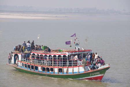 Chhota Dhulandi, Bangladesh, February 19, 2014 - Passengers cross Ganga river on Daulatdia ferry boat, Chhota Dhulandi, Bangladesh. Passenger ferry boats are often overloaded in Bangladesh.