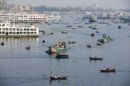dhaka: Dhaka, Bangladesh, February, 2014 - Residents of Dhaka cross Buriganga river by boats in Dhaka, Bangladesh. Thousands of people in one of the most populated capitals of the world use ferry boats daily on the way to work and back home.