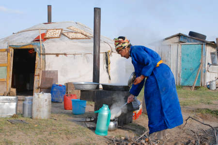 ger: Circa Harhorin, Mongolia, August 26, 2006 - Woman cooks in front of the yurt entrance circa Harhorin, Mongolia. Housekeeping in steppe for women in Mongolia is a hard task. Editorial