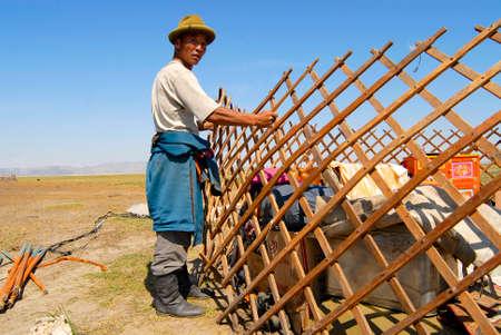 nomadic: Circa Harhorin, Mongolia, August 25, 2006 - Mongolian man assembles wooden frame of a yurt (ger or nomadic tent) in steppe circa Harhorin, Mongolia. Editorial