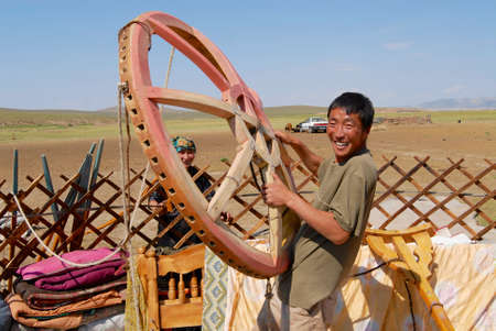 nomadic: Circa Harhorin, Mongolia, August 25, 2006 - Mongolians assemble yurt (ger or nomadic tent) in steppe circa Harhorin, Mongolia. Man holds ton (central circular part) of the wooden frame construction.