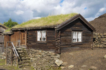 planted: Exterior of the traditional timber house of the copper mines town of Roros, Norway. Grass planted at the roof is a traditional Norwegian way of house insulation.