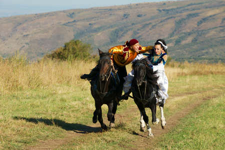 race relations: Circa Almaty, Kazakhstan, September 18, 2011 - People in national dresses ride on horseback at countryside circa Almaty, Kazakhstan.