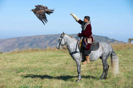 pursue: Circa Almaty, Kazakhstan, September 18, 2011 - Mongolian hunter launches golden eagle to pursue prey circa Almaty, Kazakhstan.