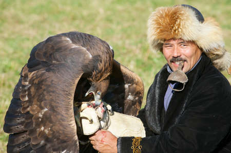 feeds: Circa Almaty, Kazakhstan, September 18, 2011 - Man feeds golden eagle (Aquila chrysaetos) circa Almaty, Kazakhstan.