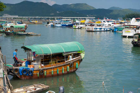 enters: Hong Kong, China, September 13, 2012 - Man enters fishing boat at Sing Kee harbor in Hong Kong, China.