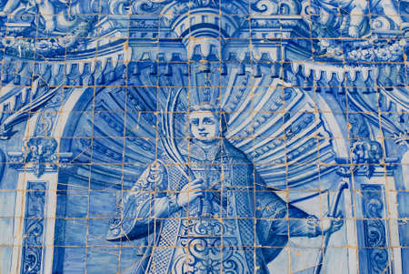 depict: Exterior detail of the Saint Lawrence of Rome church in Almancil, Portugal. Church has one of the most beautiful in Portugal hand painted tiles (Azulejo) of the 18th century at the facade. This azulejo tiles depict Saint Lawrence of Rome.