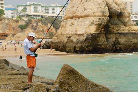 waterside: Portimao, Portugal, July 18, 2006 - Man does fishing at Praia da Rocha beach in Portimao, Portugal. Editorial