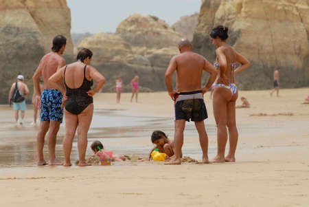 rocha: Portimao, Algarve, July 18, 2006 - People watch kids playing at the beach in Portimao, Portugal. Praia da Rocha beach is one of the most popular in Algarve, Portugal. Editorial