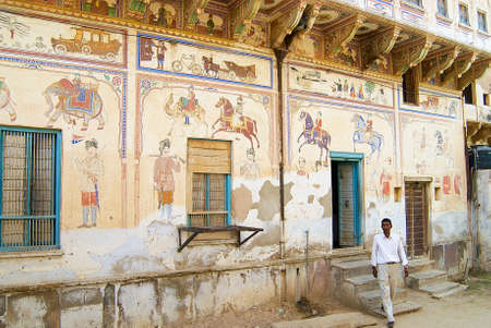 rajasthani painting: Mandawa, India, March 31, 2007 - Man exits from the building in Mandawa, India. Former bank of Bikaner building is one of the most richly decorated in Shekhawati region.