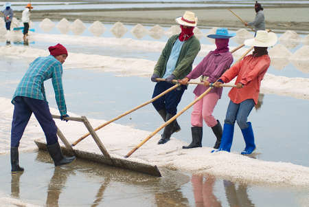 Huahin, Thailand, May 13, 2008 - People work at the salt farm in Huahin, Thailand. Salt production is one of the main industries in Huahin area, it brings modest income to many local families.