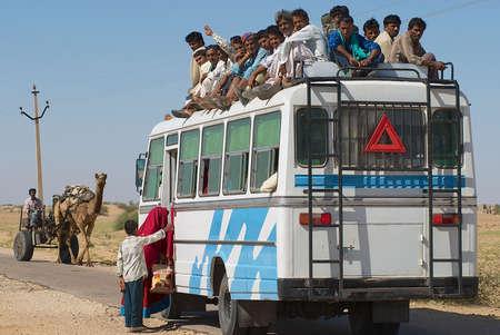 Jamba, India, 2 april 2007 - Mensen voer de streekbussen in Jamba, India. Openbaar vervoer bussen in de Great Thar woestijn, Rajasthan zijn meestal overbelast. Redactioneel