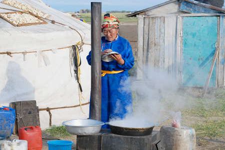 ethnographical: Harhorin, Mongolia, August 26, 2006 - Woman cooks in front of the yurt entrance circa Harhorin, Mongolia. Housekeeping in steppe for women is a hard task. Editorial