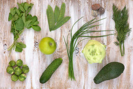 Set of green vegetables on white painted wooden background: kohlrabi, avocado, brussels sprouts, apple, cucumber, green onion, pea pods, dill, basil. Stock Photo
