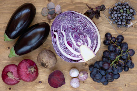 raw vegetables: Set of vegetables and berries on aged wooden background: onion, eggplant, cabbage, beetroot, garlic, basil, grape, black currant.