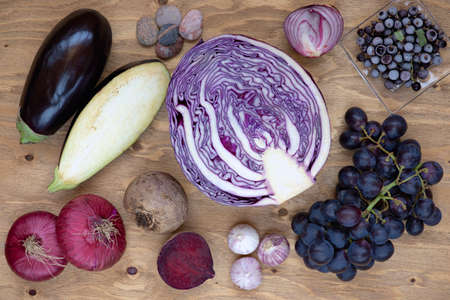 Set of vegetables and berries on aged wooden background: onion, eggplant, cabbage, beetroot, garlic, grape, black currant.
