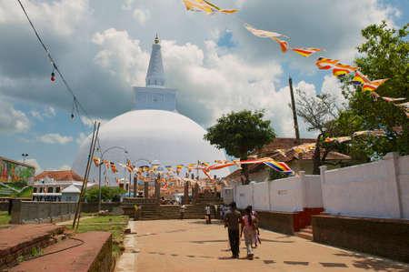 stupa one: Anuradhapura, Sri Lanka, May 19, 2011 - People go to the Ruwanwelisaya stupa in Anuradhapura, Sri Lanka. Ruwanwelisaya is a sacred place for Buddhists and one of the largest stupas in the world. Editorial