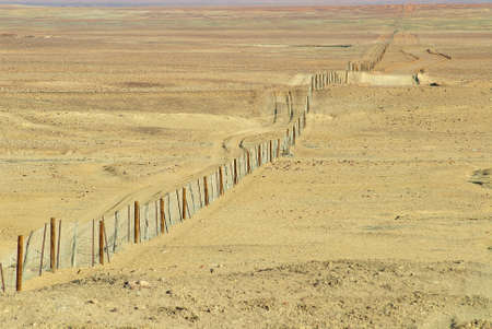 fence wire: Dingoe fence in the Australian Outback. The fence is 9600 kilometers long, it keeps the dingoe dogs out of the areas, where the sheep graze. Stock Photo