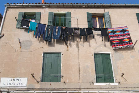 Murano: Murano Italy February 27 2007: Exterior of the facade of a residential building with washed clothes hanging outside in Murano Italy.