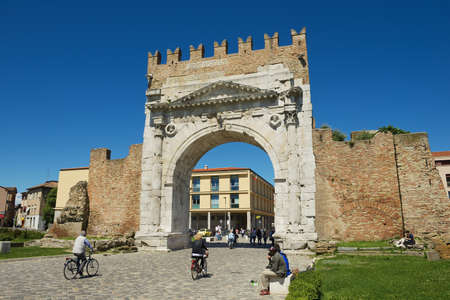 ancient pass: Rimini, Italy, May 13, 2013 - People pass under Augustus Arch - the ancient romanesque gate and the historical landmark of Rimini, Italy. Editorial