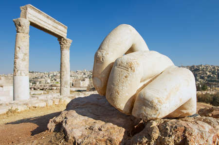 temple: Stone Hercules hand at the antique Citadel in Amman, Jordan. At the background: ruins of the Hercules temple and Amman city.