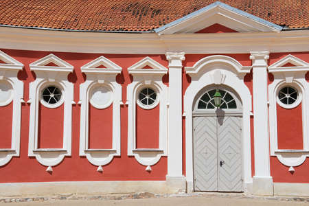 rundale: Pilsrundale, Latvia - July 27, 2015: Exterior of the red painted stables building next to Rundale palace in Pilsrundale, Latvia.