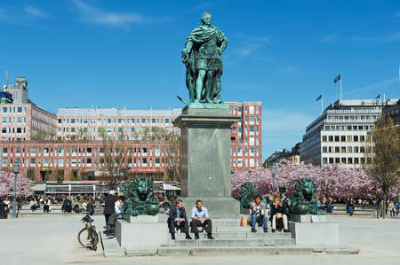 lunchtime: Stockholm, Sweden, April 28, 2011 - People enjoy lunchtime sitting under KARL XII statue at Kungstradgarden in Stockholm, Sweden.